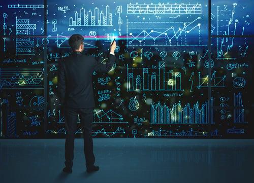 Businessman drawing business statistics on glass wall